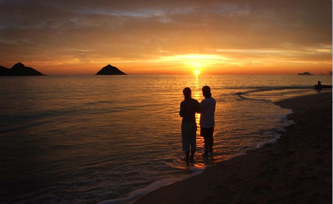 Una pareja contempla el atardecer en una playa de Kailua, Hawai.